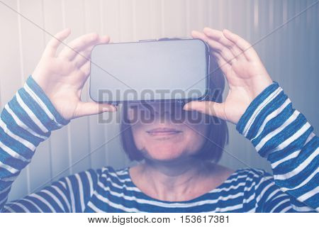 Woman watching 360 video with virtual reality headset. Female using VR goggles to enjoy futuristic multimedia content that simulates physical presence and allows interaction with environment.