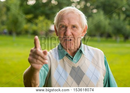 Senior man threatens with finger. Displeased old male. I disapprove this. Be ready for everything.