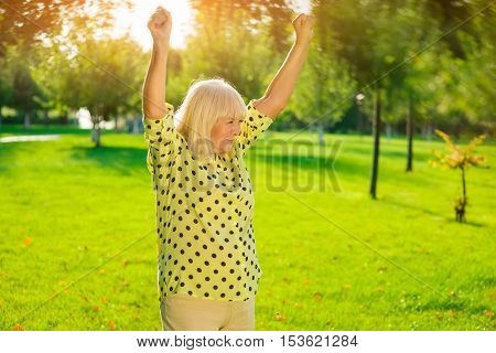 Older woman outdoors. Smiling lady with raised arms. The lucky winner. Enjoy the triumph.