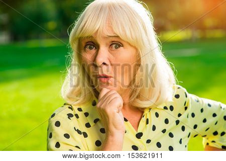 Portrait of surprised senior woman. Female holding her chin. Ideas that change life. Expectations and reality.