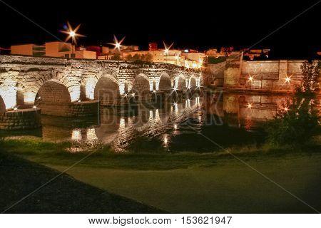 Roman bridge and alcazaba or moorish fortification at night Merida Spain