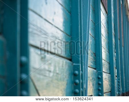 Picture of the wooden wall painted with turquoise blue colour. Old paintwork on the wall. An old country house made of planking.