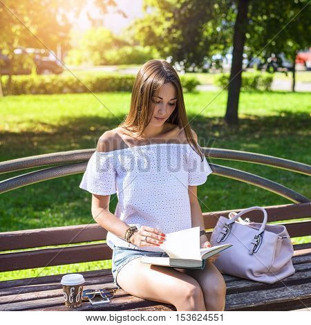 Beautiful brunette girl sitting on a bench in a summer sunny park, reading a book, enjoy your vacation, student concept, after school at recess, resting with a bag cup of coffee or tea with your smartphone
