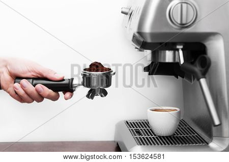 Man is using a tamper to press freshly ground morning coffee into a coffee tablet