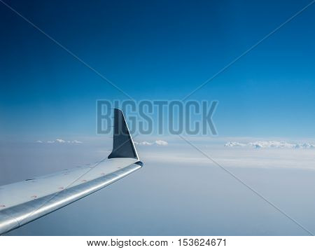 Wing of an airplane flying above the clouds. View of the sky from the window of the plane. The picture of the blue sky and airplane's wing.