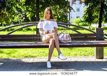 Beautiful brunette girl sitting on a bench in a summer sunny park, reading a social network, enjoy your vacation, student concept, after school at recess, resting with a bag cup of coffee or tea with your smartphone