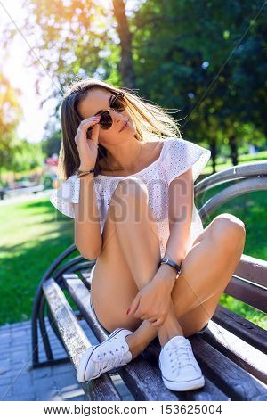 Portrait of a beautiful brunette summer in sunglasses sitting on the bench in a white blouse and denim shorts in the summer the park, enjoy your vacation, youth concept, lifestyle. Enjoying holidays
