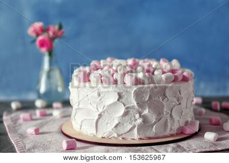 Delicious cake with marshmallows on table