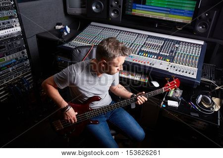 Musician playing guitar in audio studio