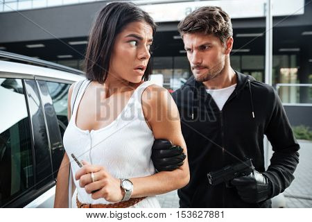 Scared young woman threatened by man criminal with gun near her car