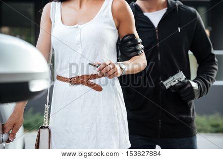 Closeup of man criminal with gun grabbing and threatening to woman outdoors