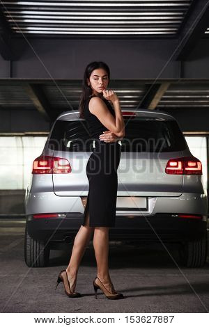 Serious pensive young businesswoman standing near car on parking