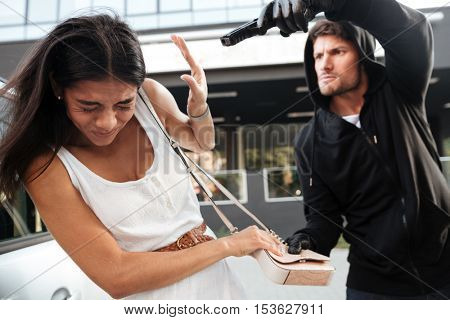Aggressive young man with gun trying to steal purse of frightened young lady on the street