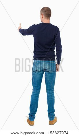Back view of  man in shirt shows thumbs up.   Rear view people collection.  backside view of person.  Isolated over white background. Man in warm jacket stretched out his hand forward.