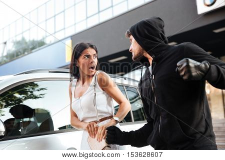 Aggressive young man thief in hoodie robbing scared young woman near her car