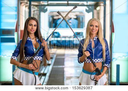 Car wash. Beautiful girls posing with pressure washers