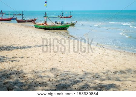 Beautiful blue sea wave and sandy beach with fishing boat. Bright and dynamic sea beach sunset with bright blue skies and colorful clouds in Hua Hin, Prachuap Khiri Khan Province, Thailand