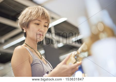 Young Woman Shopping Wine In Supermarket