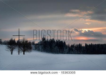 Twilight winter landscape with big cross and chalet with overhead lookout