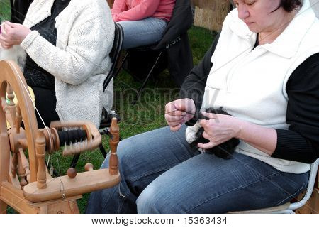 RATIBORICE, CZECH REPUBLIC - APRIL 24:  Older woman spinning wool on traditional spinning wheel - The Shepherds Festival 2010,  on April 24, 2010 in Ratiborice, Czech Republic
