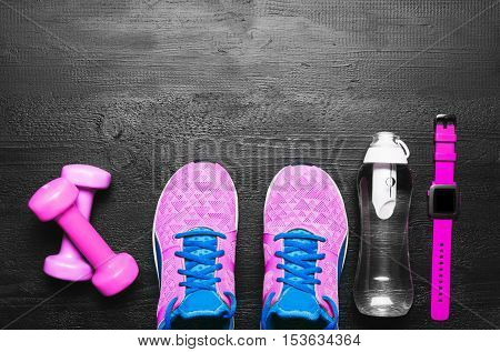 Flat lay shot of Sport equipment on black wooden background.