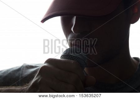 Young Man In Cap Singing Into A Microphone