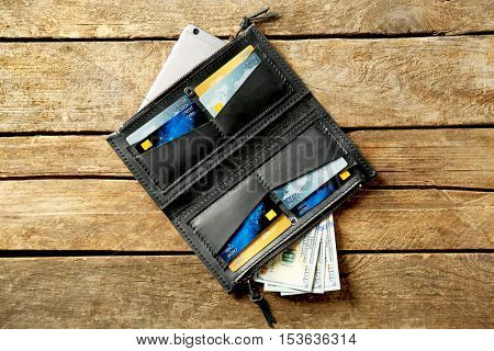 Black leather opened purse on wooden background