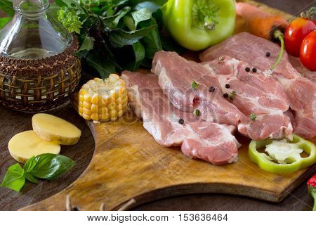 Fresh Raw Meat Pork Fillet With Vegetables On The Cutting Board. Concrete Background.