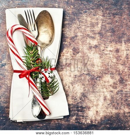 Christmas table place setting with christmas tree branches spoon knife fork and ribbon on tablecloth with copyspace. Christmas holidays background