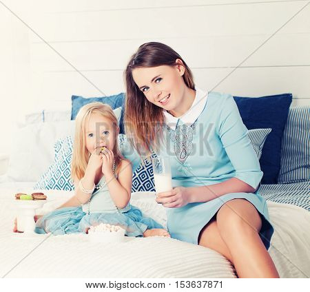 Mother and Daughter Sitting on the Bed Eating Sweets and Drinking Milk