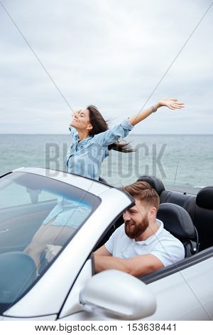 Young couple in love on road trip driving in convertible car
