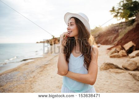 Cheerful young woman walking on the beach and looking at the sea