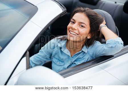 Portrait of young beautiful girl driving cabriolet