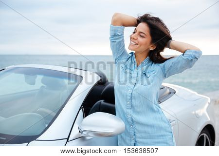 Young brunette woman standing next to her new car at the seaside
