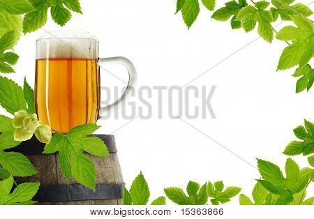 Fresh hop frame with vintage glass of beer on old barrel, isolated on white background