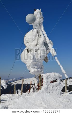 Antenna for multiple purposes frozen and covered by snow fenced by damaged barbed wire