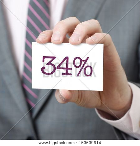 34% written on a card held by a businessman