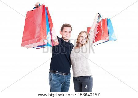 Happy Couple Holding Up Bunch Of Shopping Bags