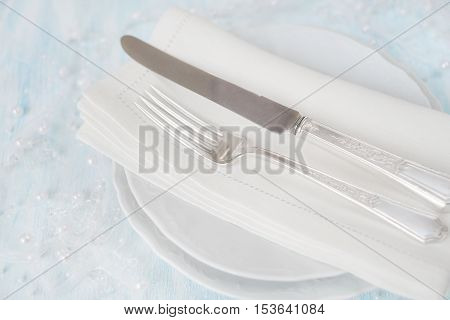Festive table: silver knife and fork as well as a linen napkin are on the white porcelain plate