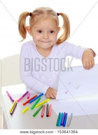 Pretty little blonde girl drawing with markers at the table.Girl happily shows a white sheet of paper with the drawing.