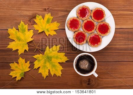 Coffee and cookies autumn leaves on a wooden table.