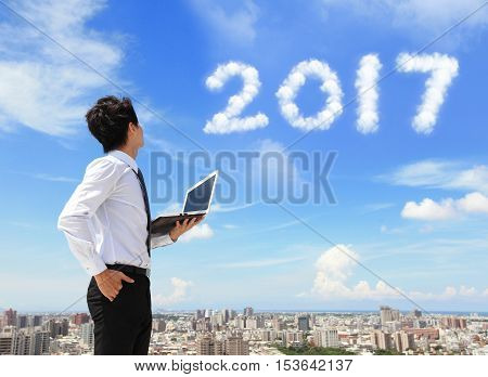 Young business man using laptop and look to 2017 year text with blue sky and cloud and cityscape in the background asian