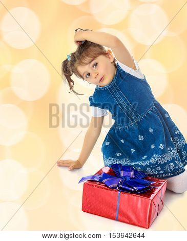 Charming little girl in a blue dress with short sleeves , kneeling around a red box with a blue bow.Brown festive, Christmas background with white snowflakes, circles.