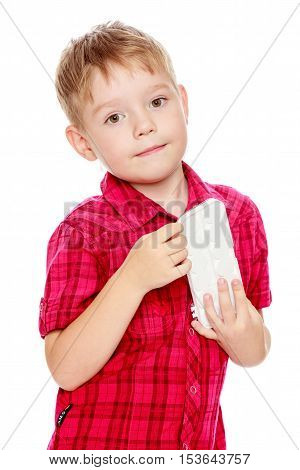 Cute little boy in a red shirt holds his box of watercolors.Isolated on white background