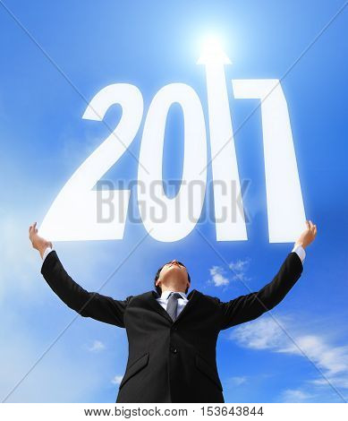 Happy new year - Business man holding 2017 new year imagination with sky and cloud asian