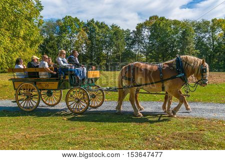 Lancaster PA USA - October 9 2016: Visitors ride in a horse-drawn wagon at the Landis Valley Farm and Museum during the annual Harvest Day event.