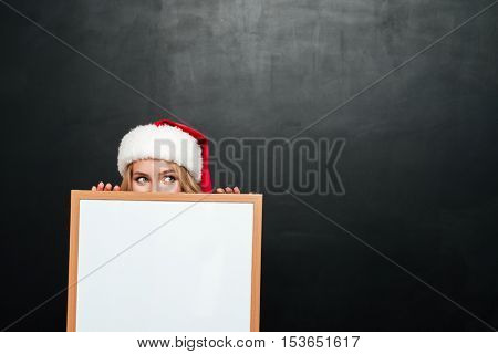 Funny young woman in santa claus hat hiding behind blank white board