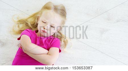Angry Girl Lying On White Wooden Floor
