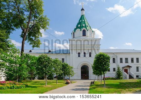 KOSTROMA RUSSIA - JULY 20 2016: Unknown woman visits Holy Trinity Ipatievsky male monastery Gate Church of Chrysanthos and Daria (XIX century) Kostroma Russia