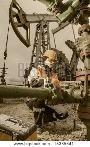 Woman engineer in the oilfield repairing wellhead with the wrench and wearing orange helmet and work clothes. Pump jack background. Oil and gas concept. Toned.